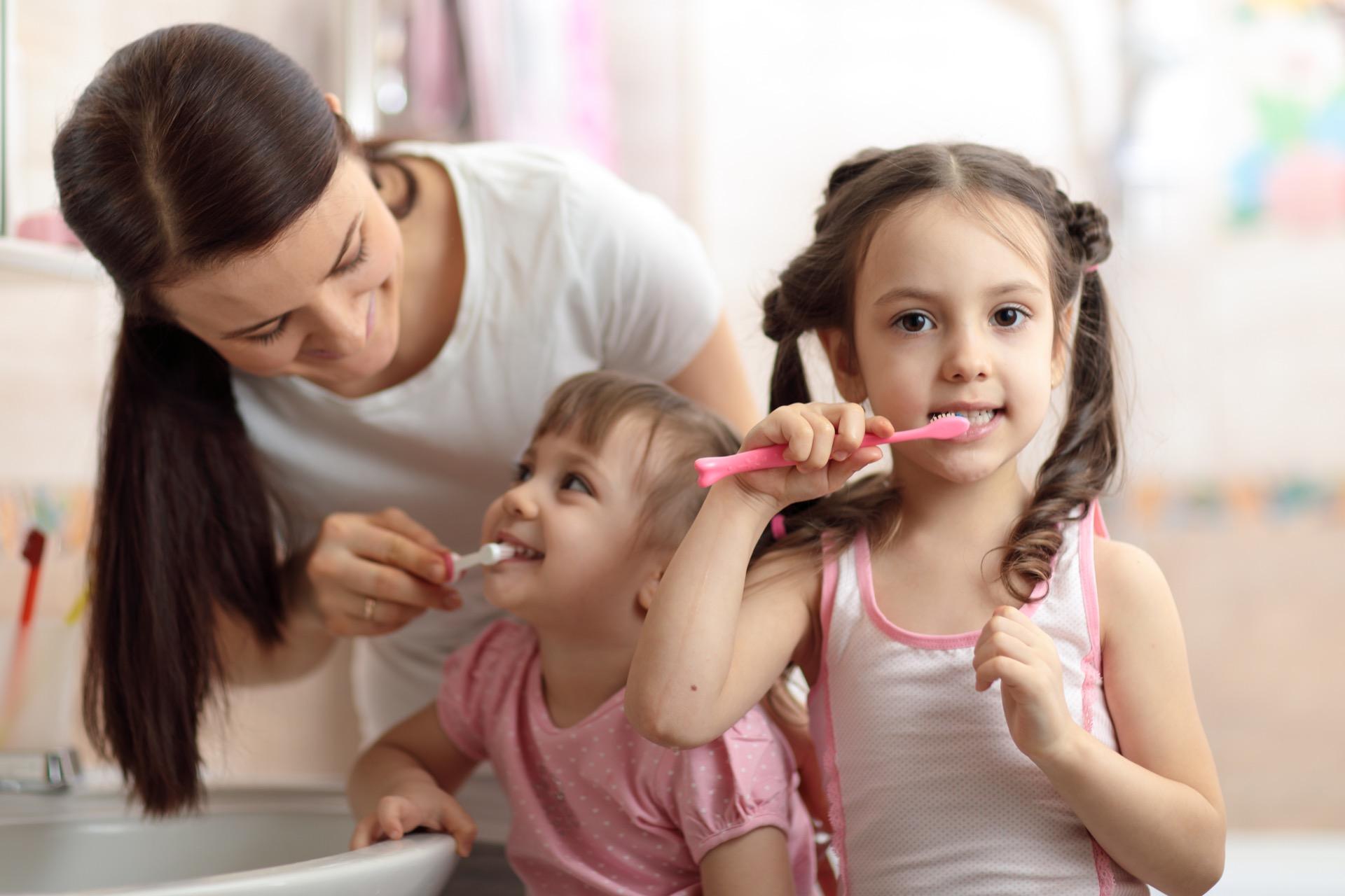 Parent teaching kids good oral hygiene
