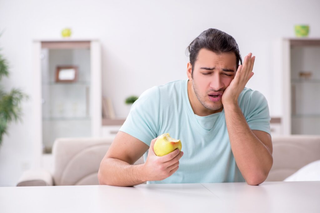 Young man experiencing pain when chewing